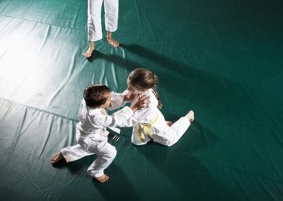 Children practicing Jiu-Jitsu, instructor watching